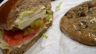 Cheese sub (sandwich) and chocolate chip cookie.